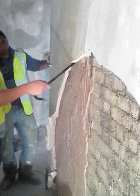 Workers breaking off detached plaster from old walls.
