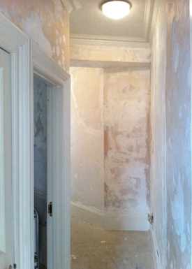 A corridor with even walls after general plaster repairs.