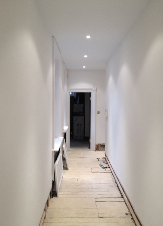 A corridor with a new false ceiling and smooth walls following repairs using a fiberglass rendering mesh and skim plaster.