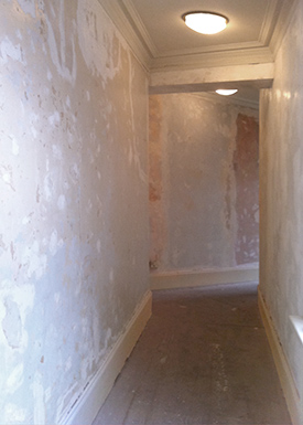 A stripped out apartment corridor being prepared for renovation.
