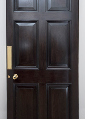 A restored Georgian 6 panel door using a dark wood stain and French polishing.