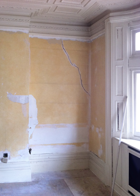 Stripped back walls before a renovation revealing cracks and defects.