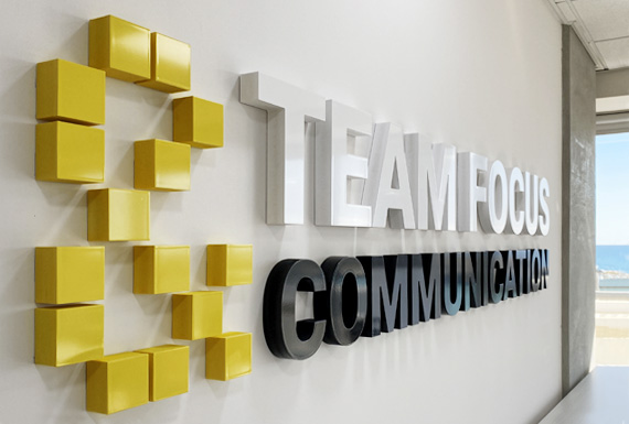 A custom 3D acrylic sign with company brand values which says teamwork and communication.
