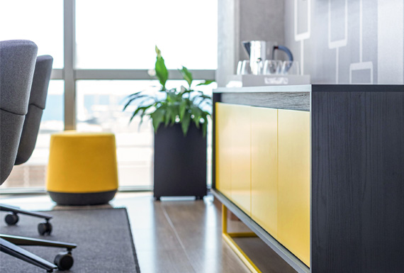 A modern yellow and black sideboard in an office conference room.
