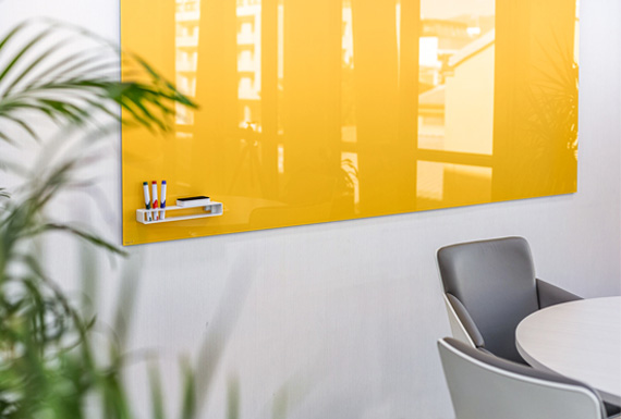 A yellow glass board in a modern office space.