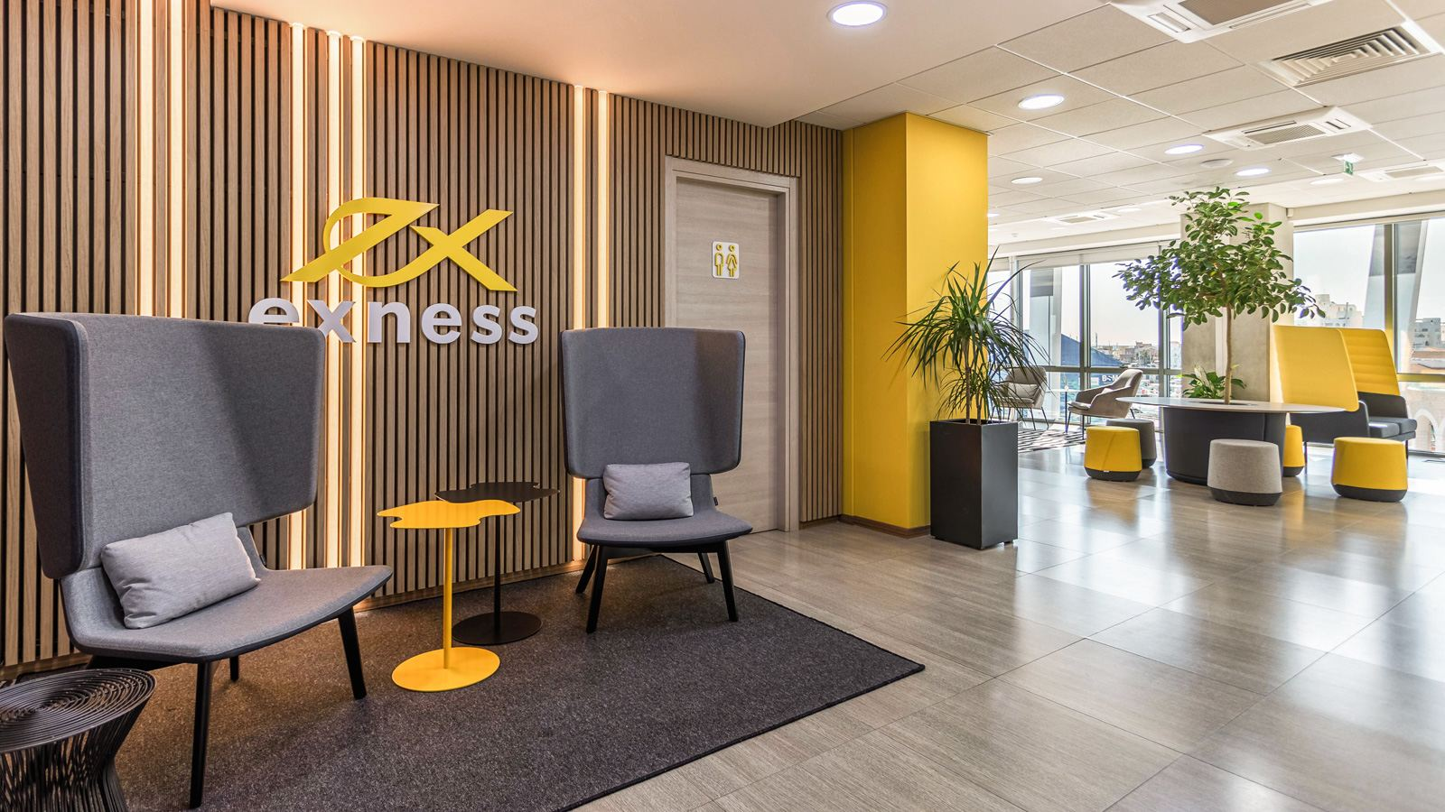 A modern and branded office interior with a black, grey and yellow colour theme, designed for Exness Forex company.