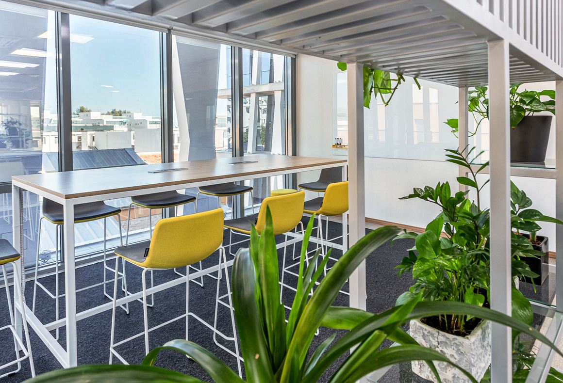 A collaboration area at Exness office with a high table, yellow stools, a glass board and a metal bookcase divider with plants.