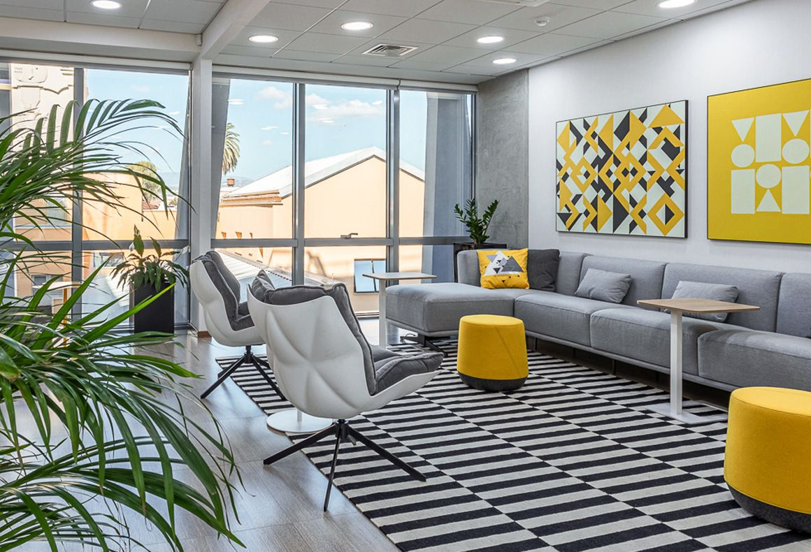 An office lounge at Exness with a black and white rug, grey sofa, iconic armchairs and yellow accents.