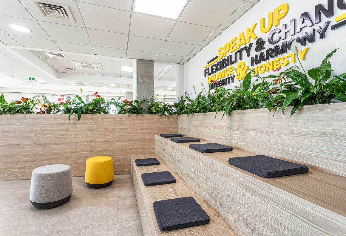 A collaboration area with custom-made tiered seating and plants for the office design of Exness.