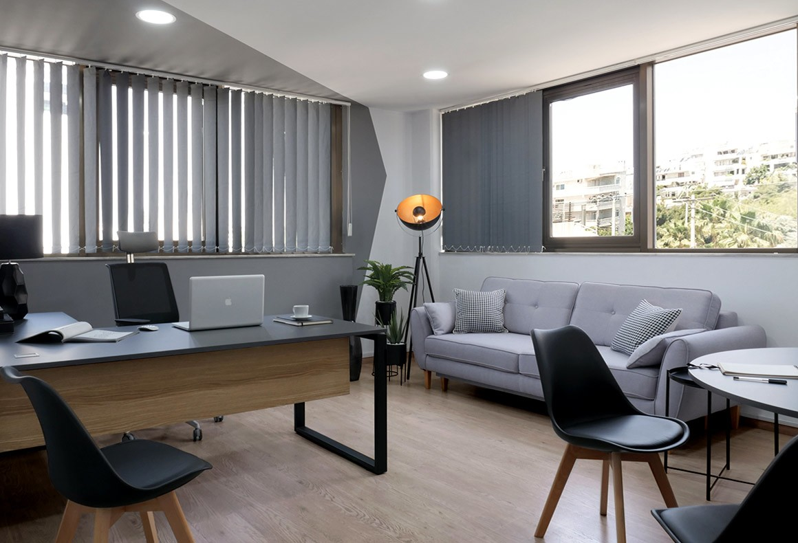 A masculine yet cozy executive office design in shades of grey and black with wood accents and a signature floor lamp.