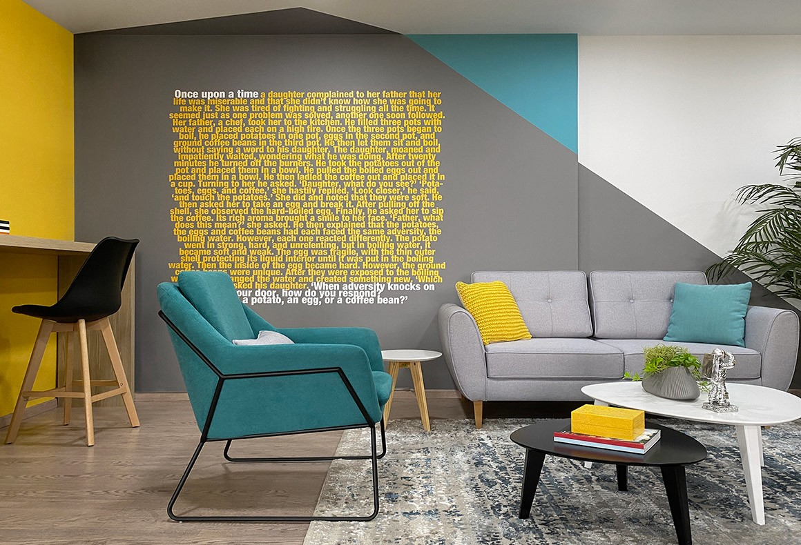 LearnWorlds office interior with Scandi furniture, geometric wall paint designs and a motivational quote on the wall.