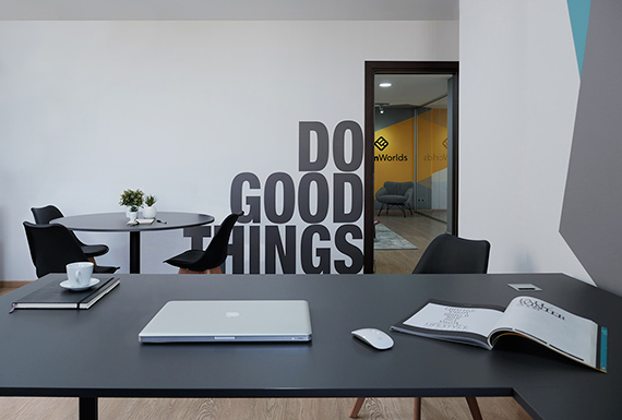 A view of an executive office desk with a large quote on the wall in the background.
