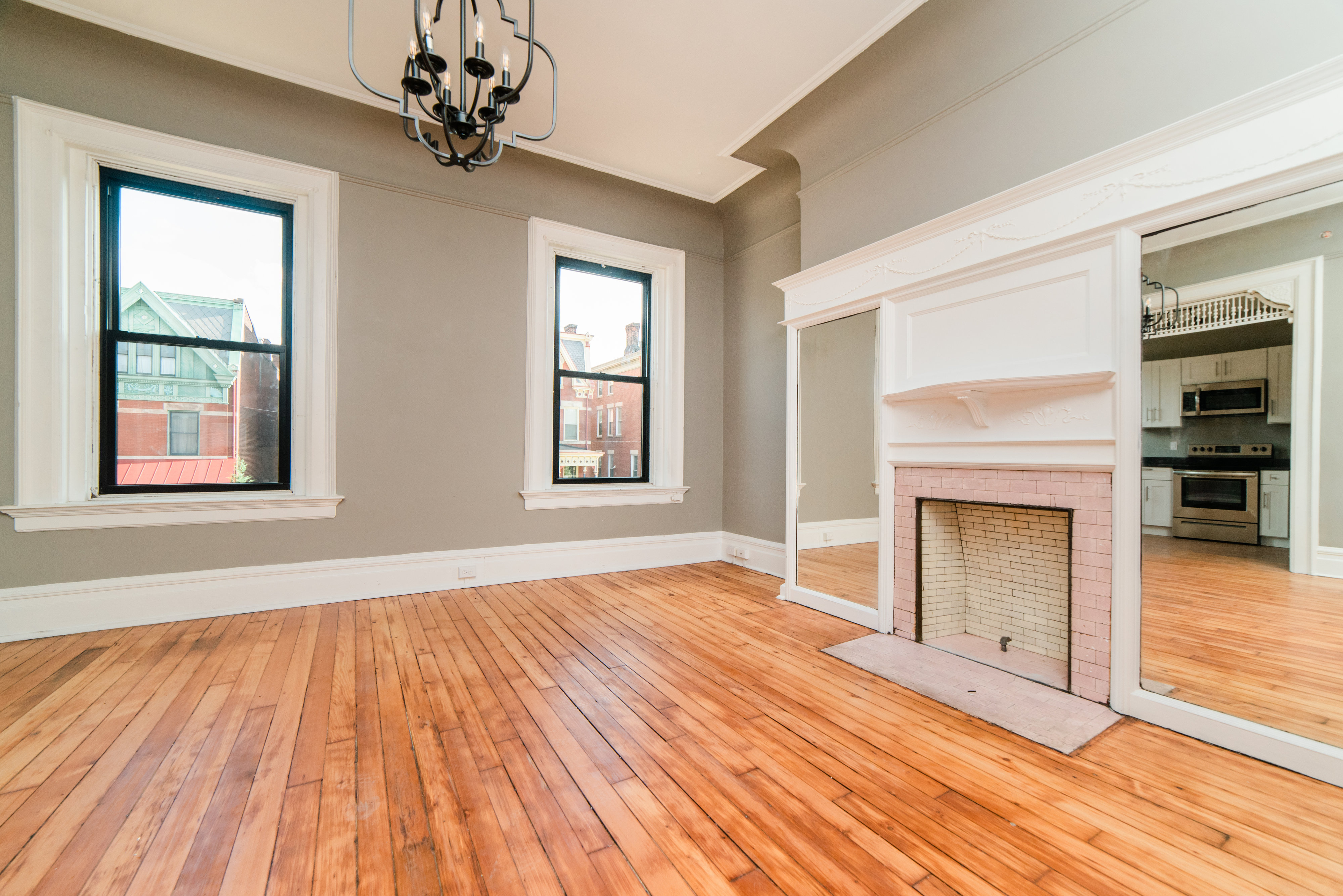 Renovated living area with a fireplace and windows facing the street
