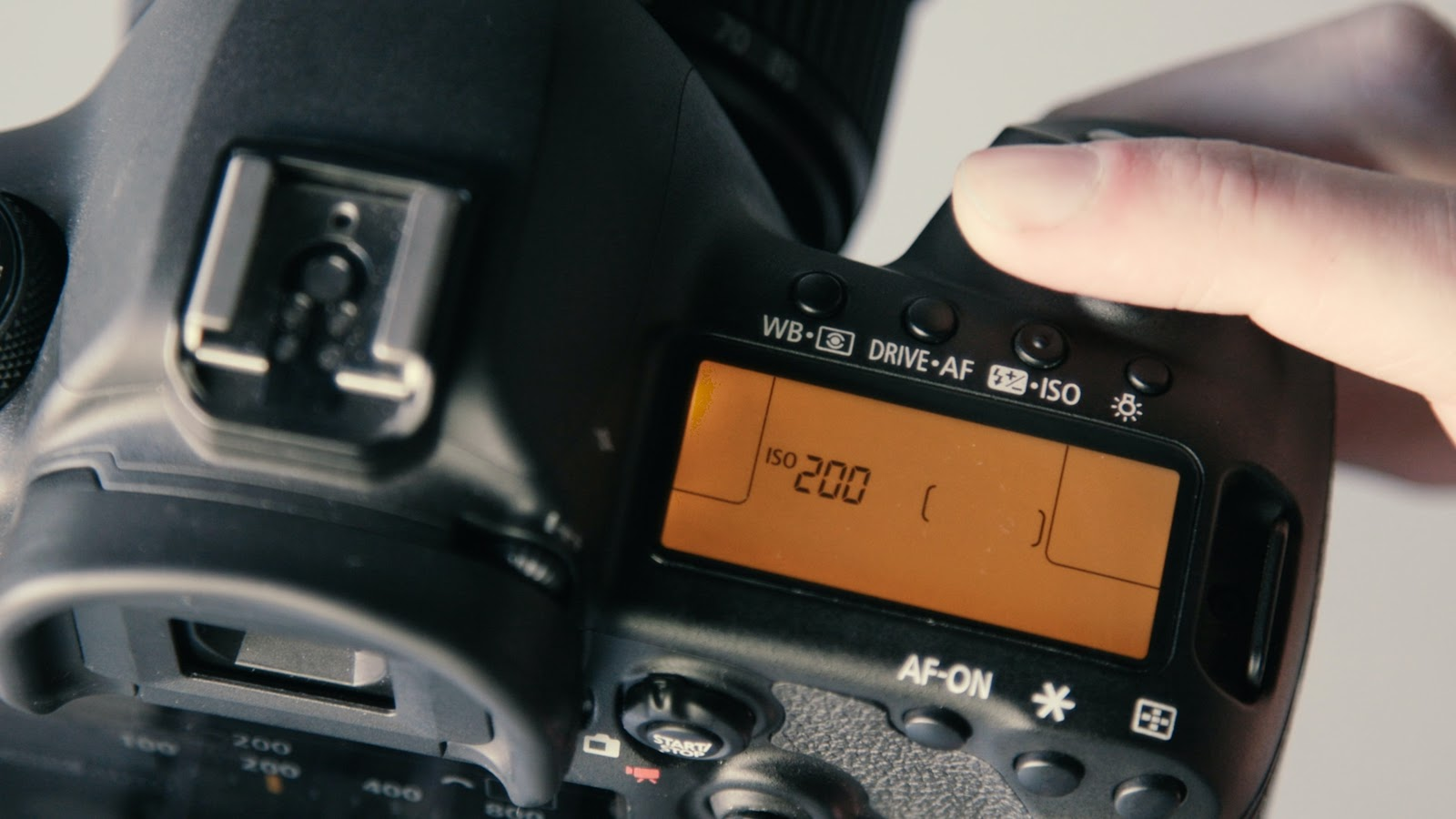 up close photo of a DSLR camera with settings displayed