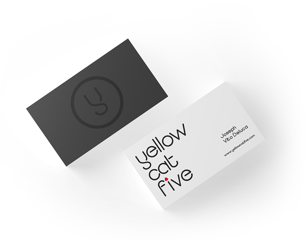 """Business cards on a table. One stack shows the front side of the business card; black with the letter """"Y"""" imprinted on it. The other stack shows the information side of the business card, with the words """"Yellow Cat Five"""" against a white background, with name and contact details on the right hand corner of the card."""