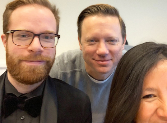 A 'selfie' photo of two men and one woman smiling up close. The man on the left is a white male with red hair and beard. He is wearing brown rimmed glasses. The man in the middle is a white male, wearing a grey sweatshirt, he has short brown cropped hair. The woman on the right is a Latina female with dark brown hair and dark skin, a portion of her face has been cut off by the frame.