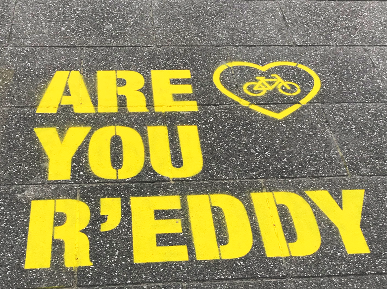 """The words """"Are you r'eddy"""" have been spraypainted in bright yellow on grey asphalt in large capital block letters. In the top right a yellow heart with a bicycle in the center has also been spray painted in yellow."""