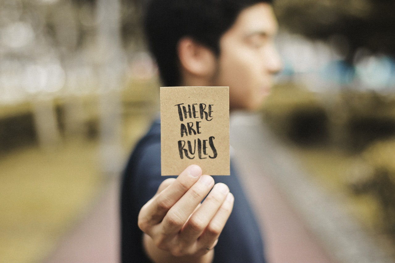 "Man holding card saying ""There are Rules"""
