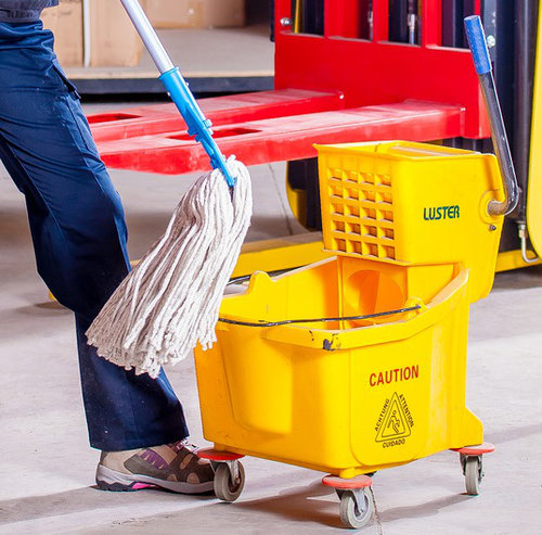 Janitor's leg in an active stance- mop moving toward a yellow commercial mop bucket.