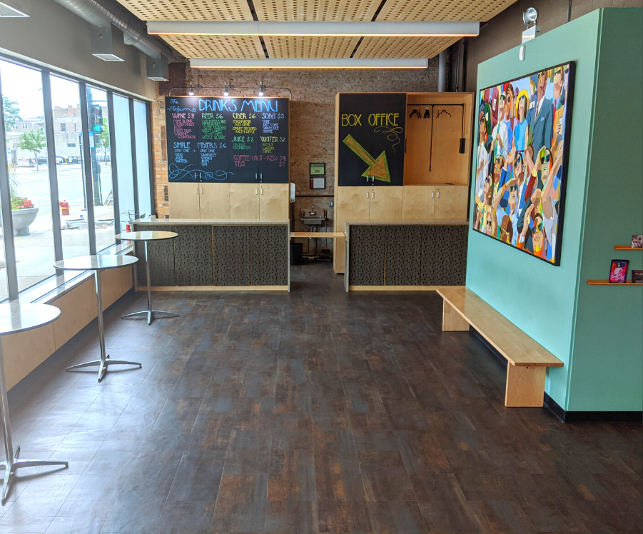 Spacious theater lobby with dark wood laminate floors, a teal accent wall with a colorful mural on it.