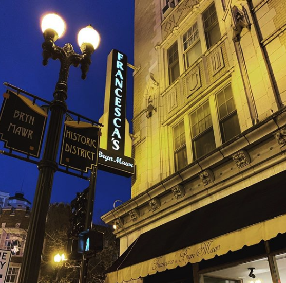 """Nighttime photo of the exterior of Francesca's showing """"Edgewater Historic District"""" banners on a classic-looking street light."""