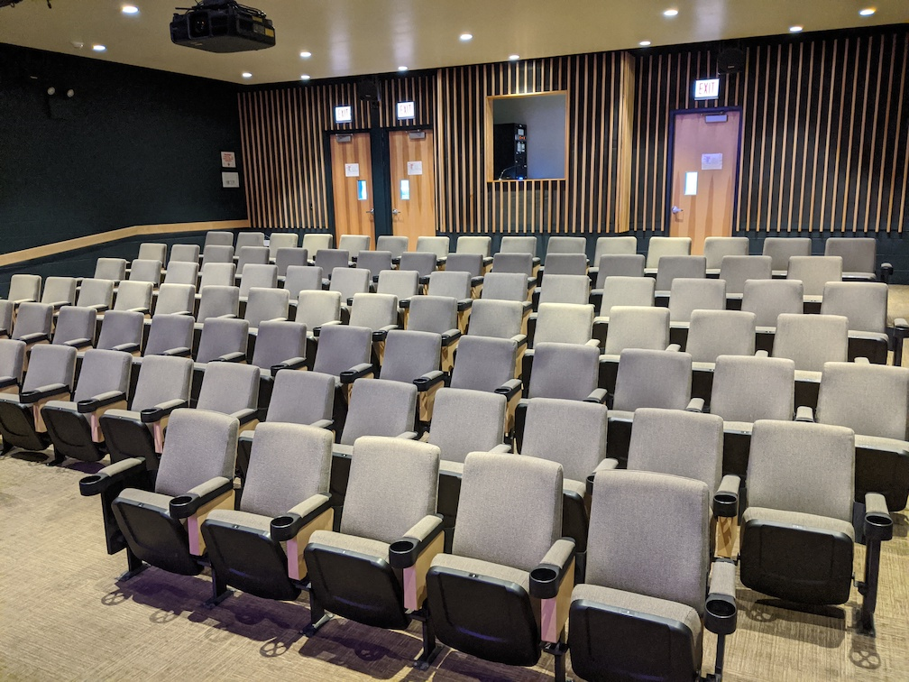 house of a proscenium theater, grey chairs, well-lit, 3 doors at the far end