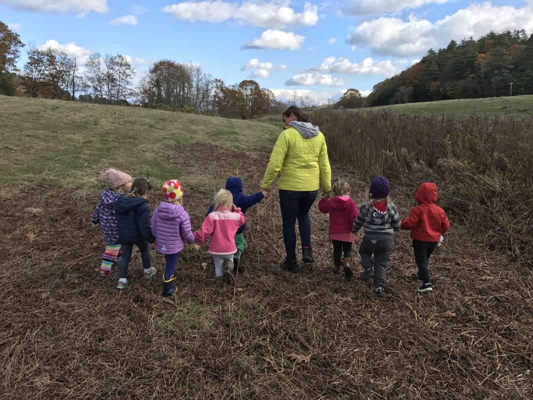 Preschool teacher and chidren holding hands walking in field