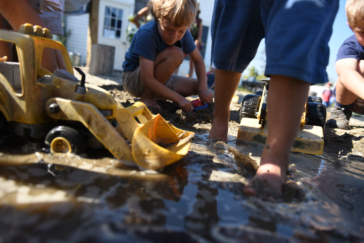 Picture of children playing mud with toy construction vehicles