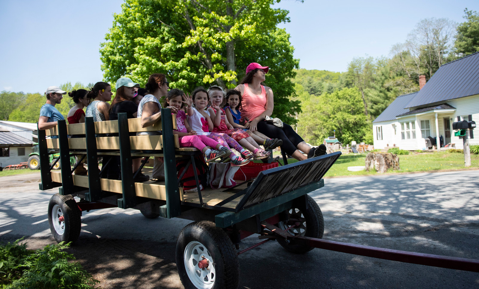 children and adults riding in wagon