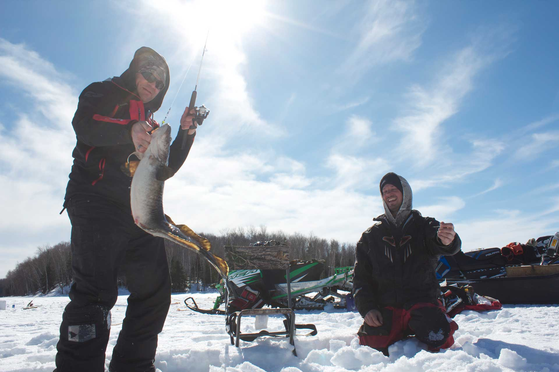 Two men ice fishing in snow with snowmobiles behind them. The man on the left has caught a fish. Both men are smiling.
