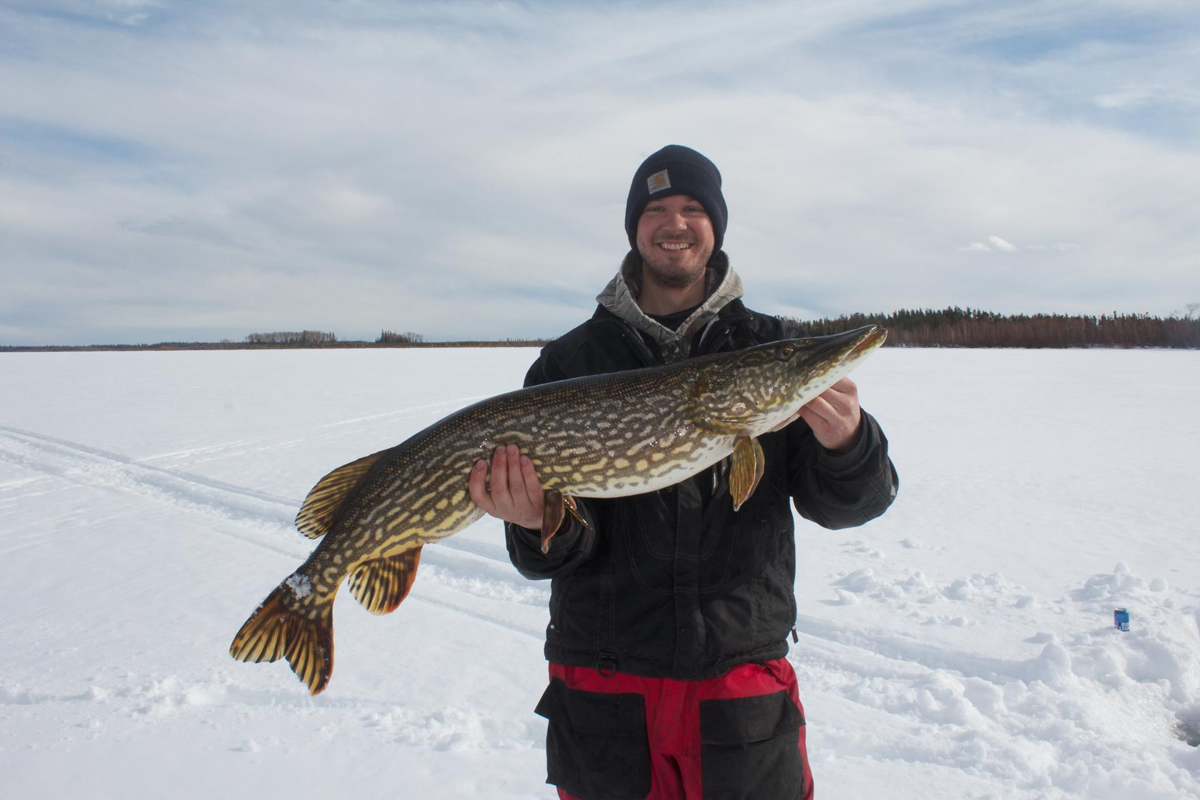 A man wearing a black winter jacket holds a northern pike on a frozen, snow-covered lake.