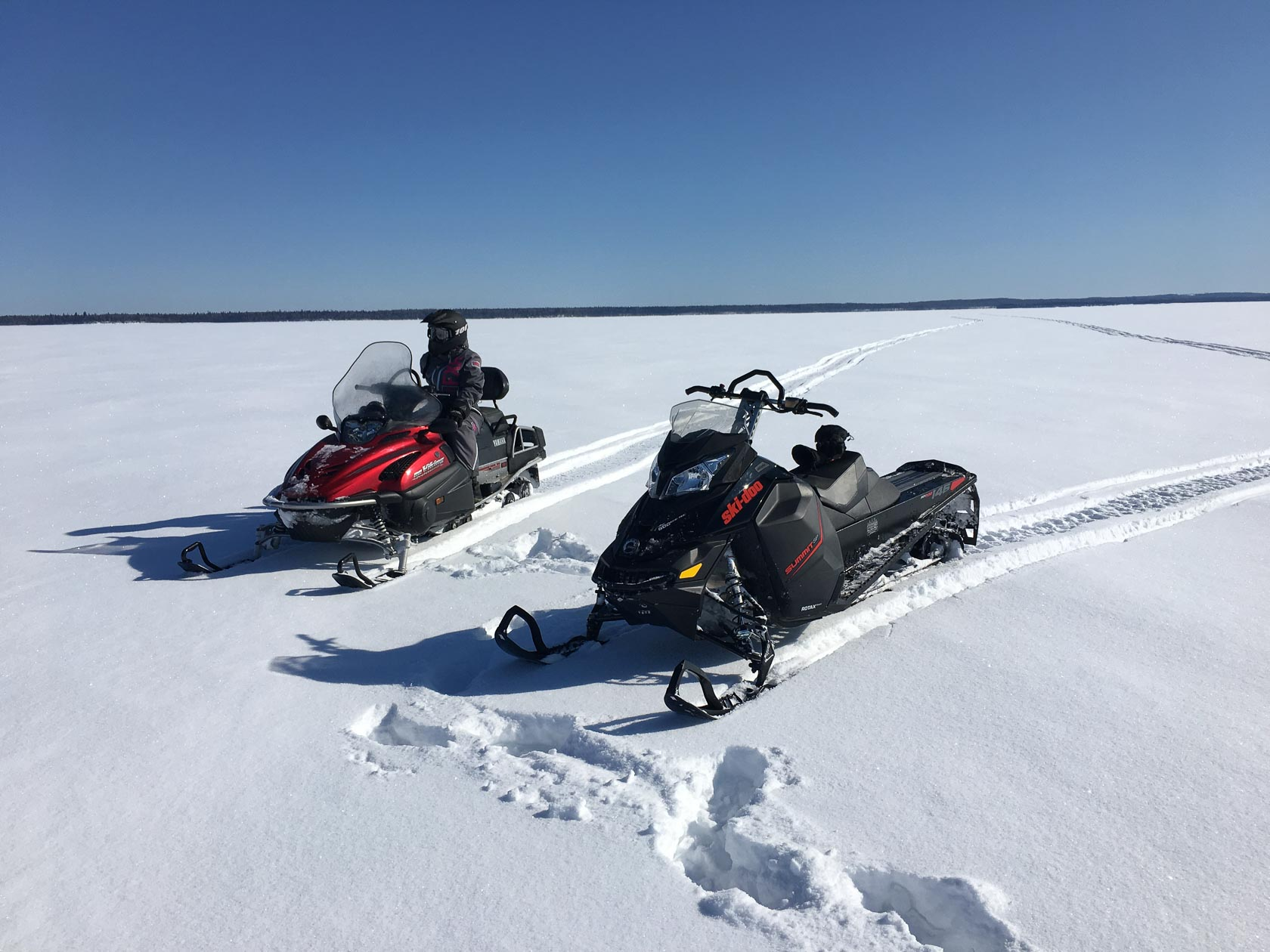 Two snowmobiles sit parked in the middle of a snow-covered frozen lake near Smoothstone Lake Lodge in Saskatchewan, Canada.