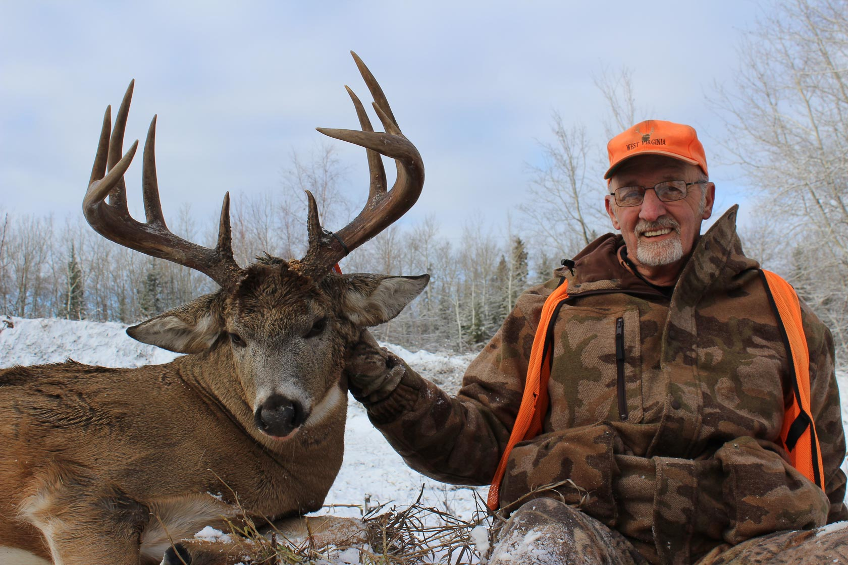 An older gentleman wearing camouflage, an orange safety vest, and an orange hat sits next to a whitetail deer near Smootsthone Lake Lodge in Saskatchewan, Canada.