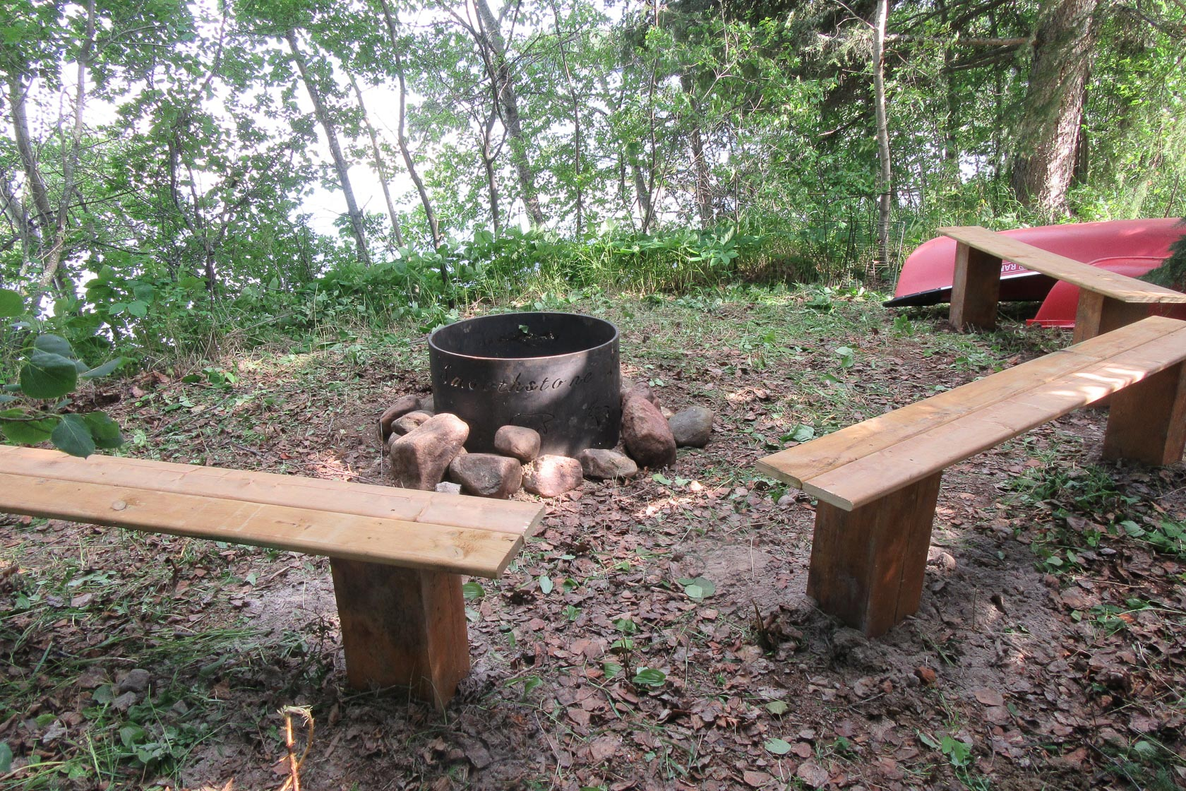 A fire pit on the shores of Smoothstone Lake Lodge in Saskatchewan, Canada. There are two wooden benches and rocks around the metal pit.