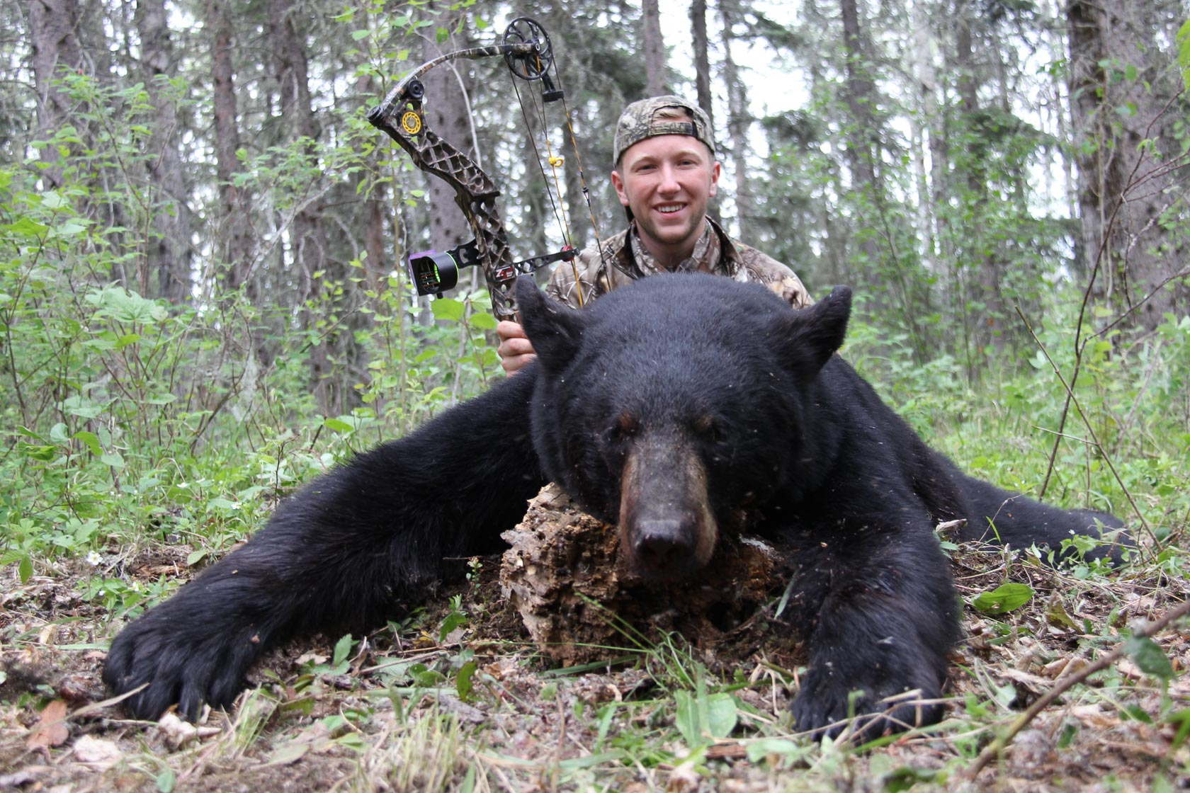 A young man holding a bow kneeling behind a black bear in the bush near Smoothstone Lake Lodge in Saskatchewan, Canada.