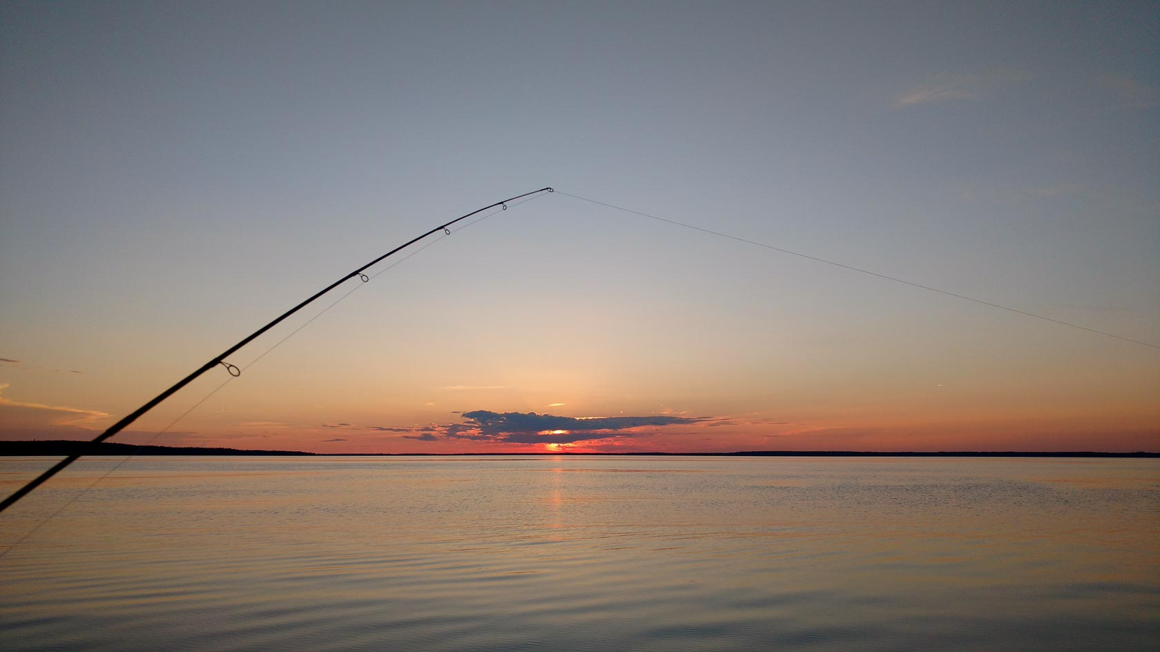 The sun sets over Smoothstone Lake in Saskatchewan Canada with a fishing pole in the foreground.