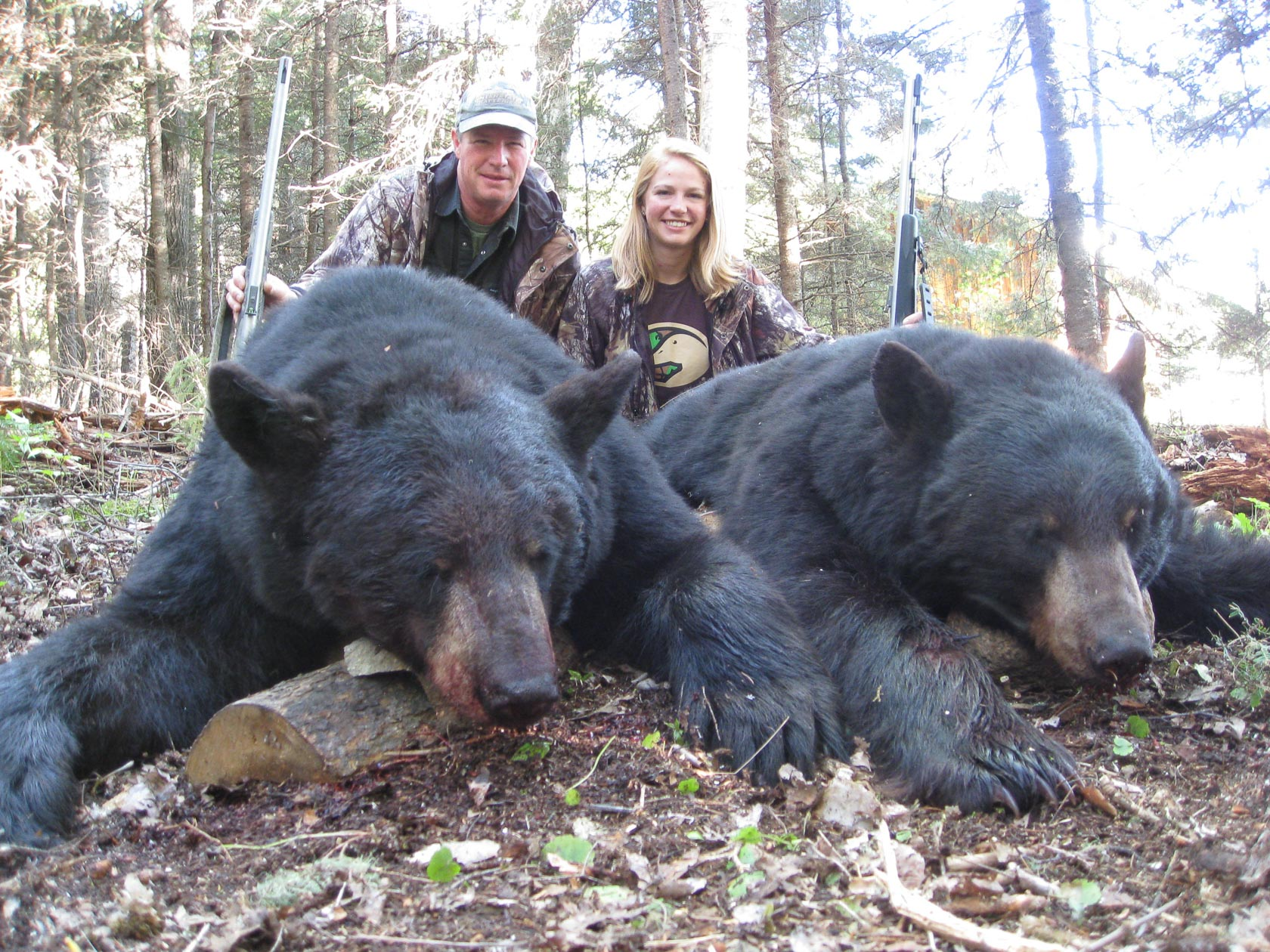 A man and a woman holding guns kneel behind two large black bears.
