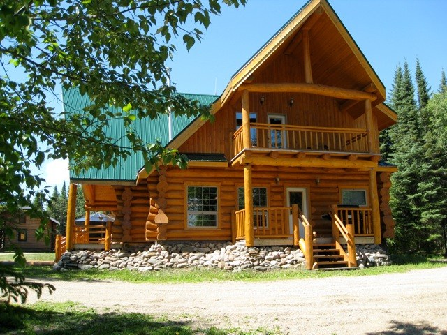 An exterior view of the 2-storey log cabin main lodge at Smoothstone Lake Lodge in Saskatchewan, Canada.
