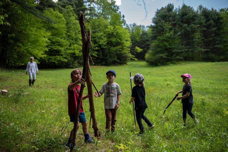 Preschool children building a teepee