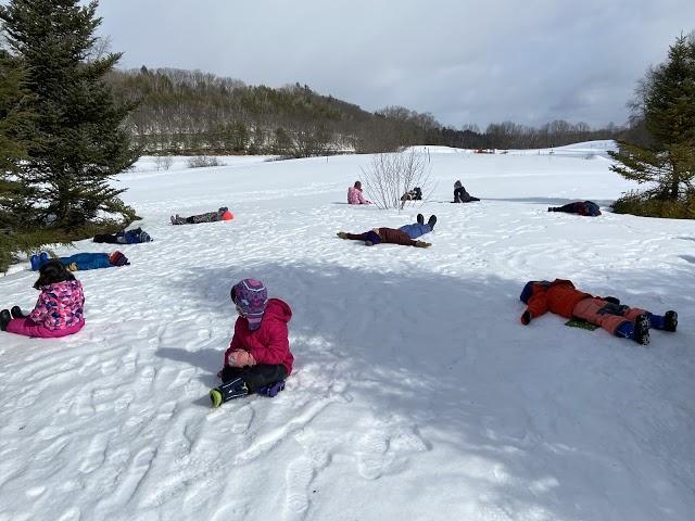 Preschool children lying in the snow