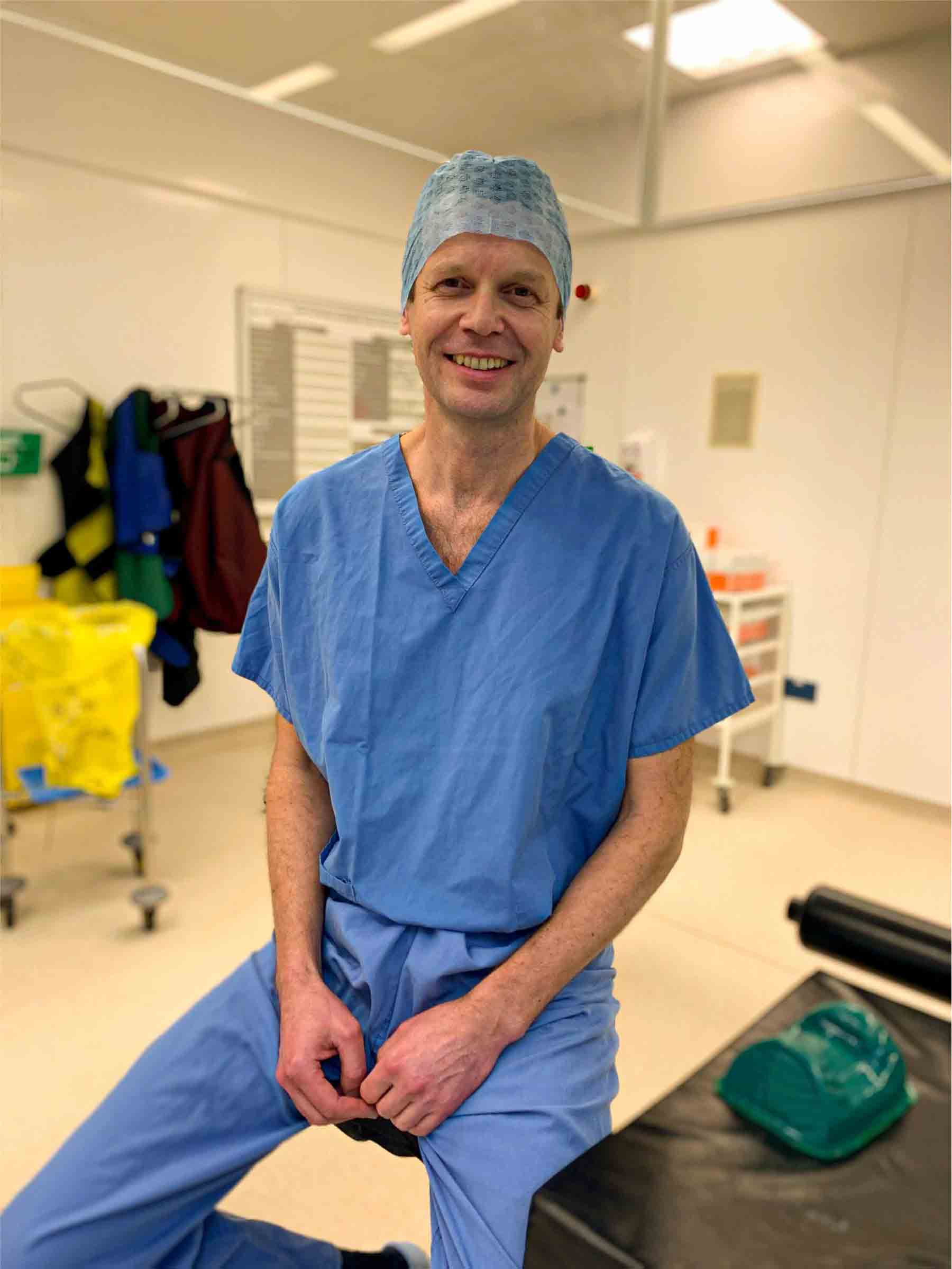 Dr Matija Krkovic, the best limb reconstructive surgeon in UK, sitting in theatre in blue scrubs