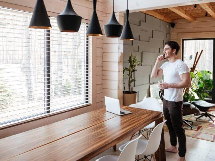 junger Mann am Telefon an einem großen Esstisch