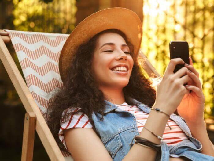 junge Frau im LIegestuhl am Smartphone