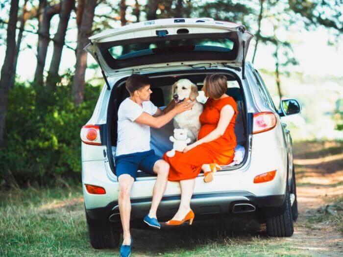 Familie mit einem Hund im Kofferraum