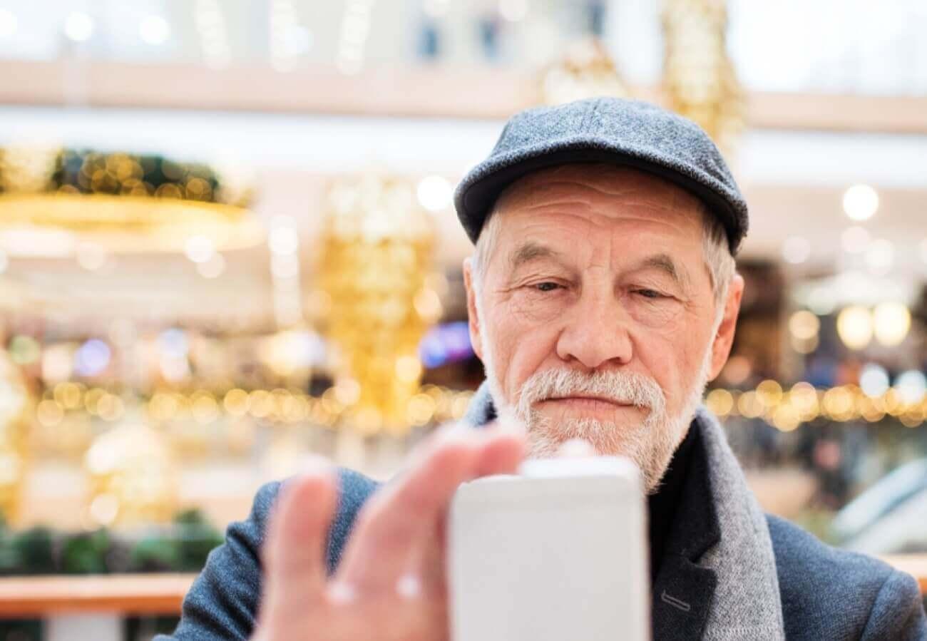 Älterer Herr beim Preisvergleich mit dem Smartphone