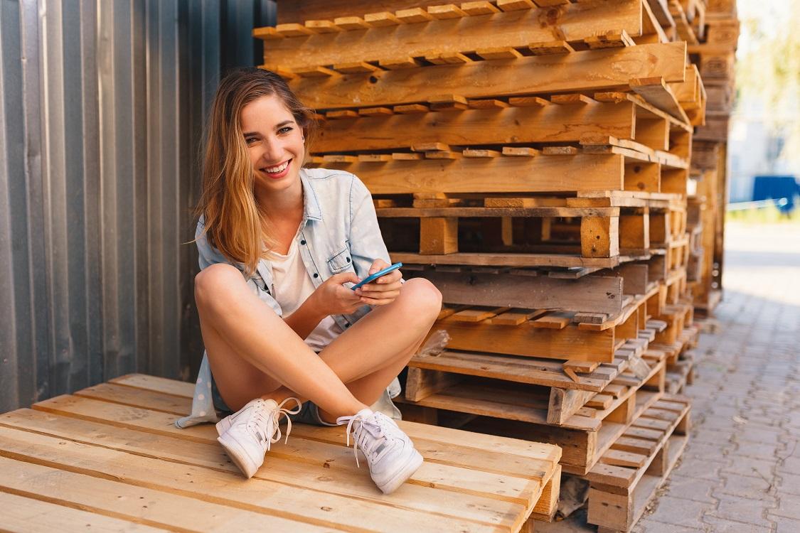 Junge Frau mit Smartphone, sitzend auf Europaletten