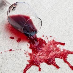 Rotweinfleck auf einem weißen Teppich