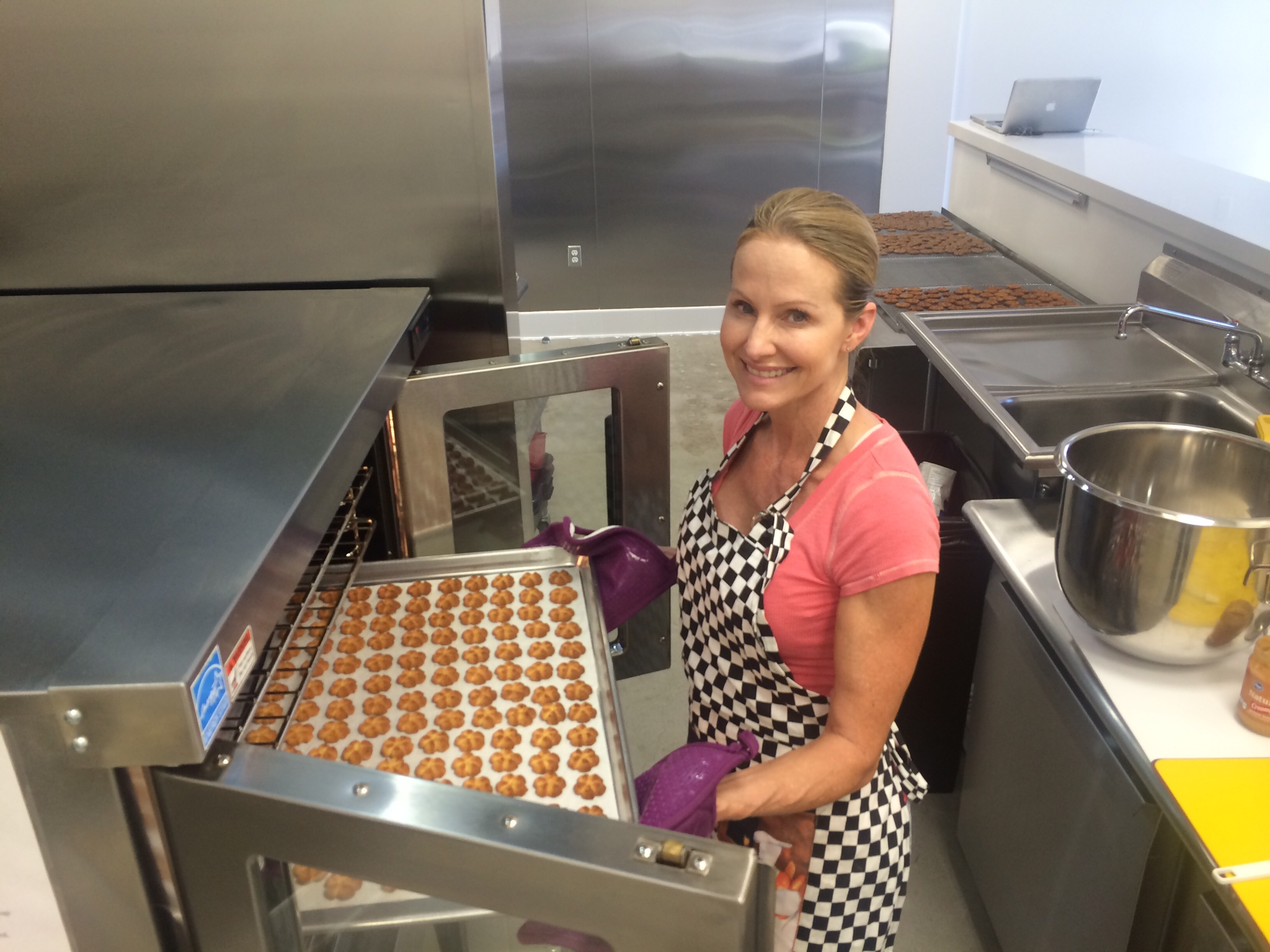 Woman in Kitchen smiling and baking dog treats