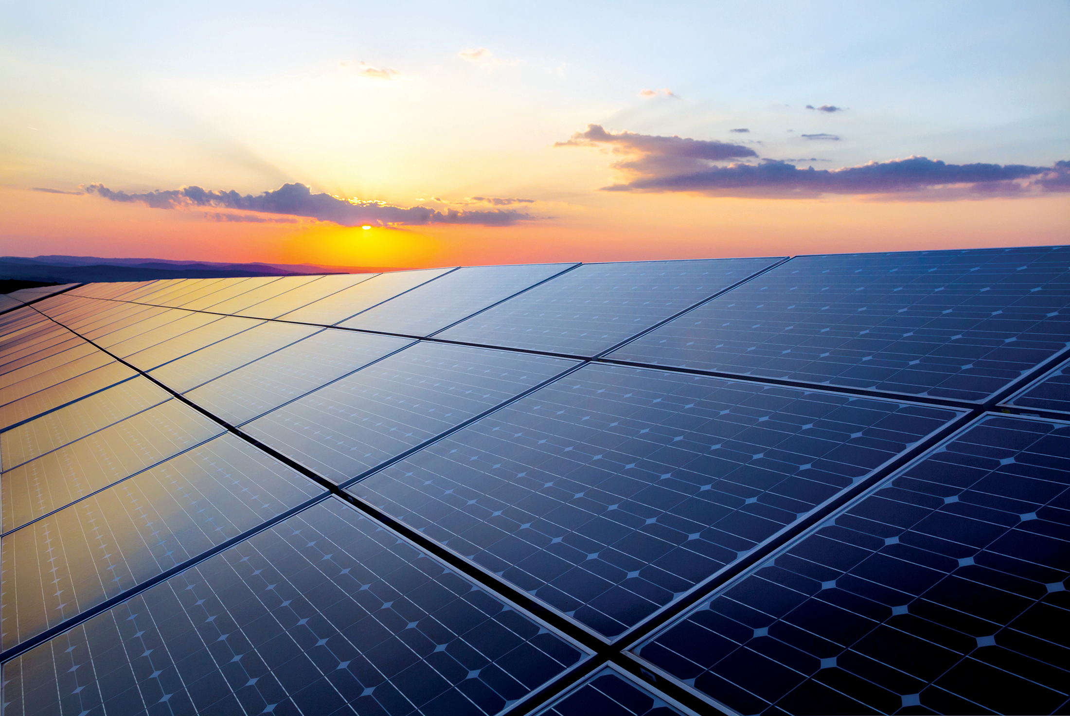 Solar power cells in foreground with sunset in the background