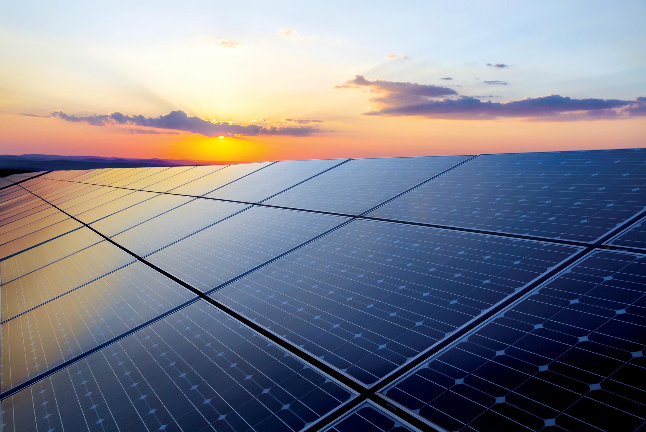Piles solaires au premier plan et coucher de soleil à l'arrière-plan